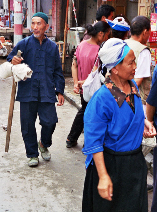 Faces of Chong'an Market Old man in Mao suit and Miao lady browsing the market