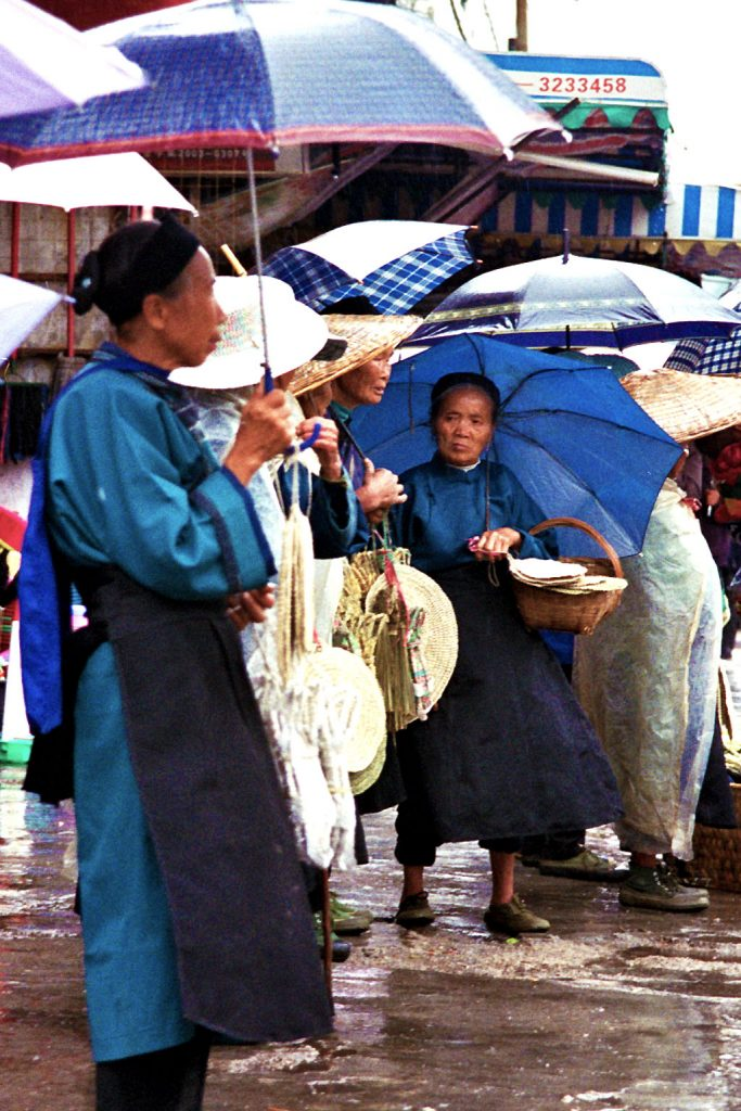 Anshun Sunday Market: 安顺星期七农民市场 ladies waiting to go home in the rain