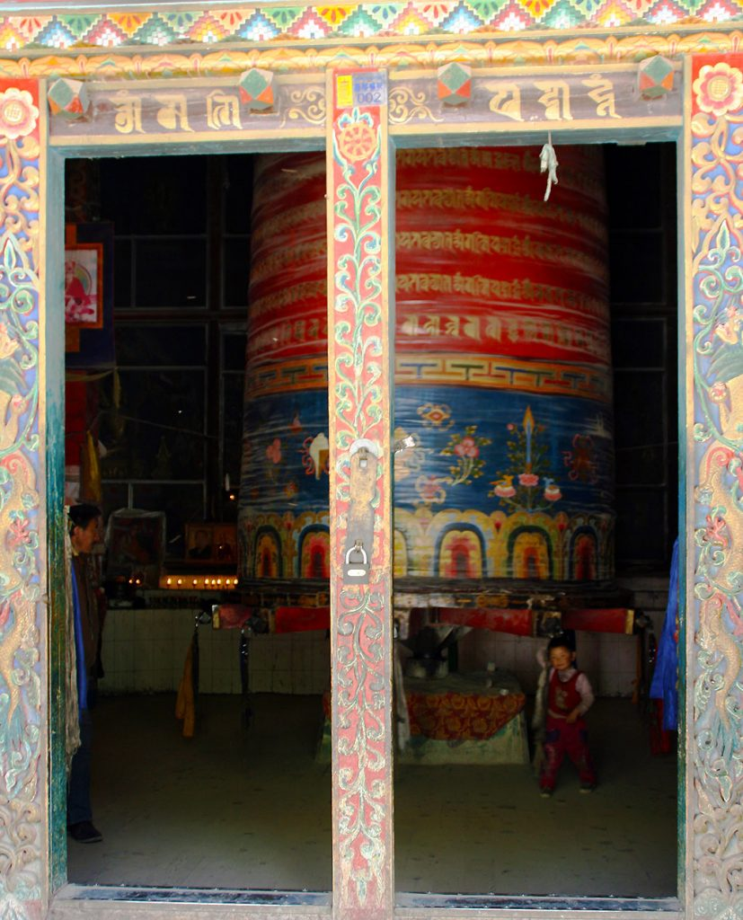 Prayer wheel and pilgrims at the The Original Yushu Seng-ze Gyanak Mani Wall before the 2009 Earthquake