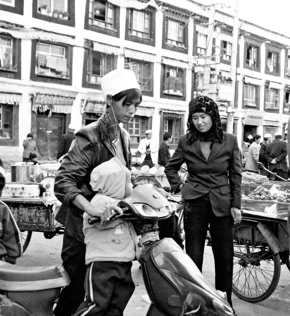 Muslim ladies in Lhasa with child. Hui Minority in a Street in Lhasa