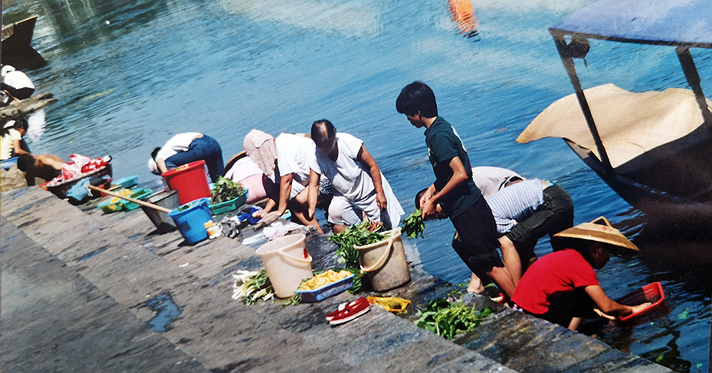 You wont see this now Reatuarant staff washing your veggies in the river Fenghuang 2003